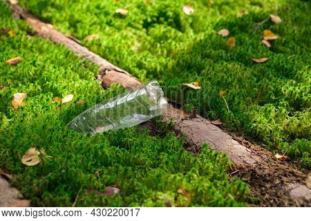 A Plastic Bottle Lies In The Sun On A Forest Moss With A Fallen Old Tree Trunk. The Concept Of Envir
