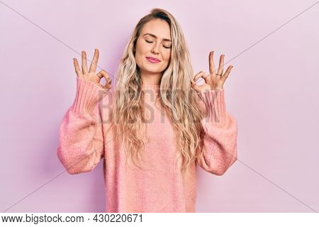 Beautiful young blonde woman wearing pink sweater relax and smiling with eyes closed doing meditation gesture with fingers. yoga concept.