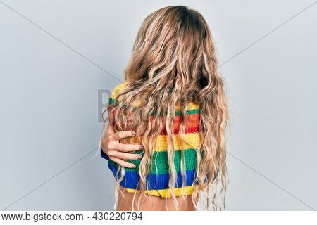 Beautiful young blonde woman wearing colored sweater hugging oneself happy and positive from backwards. self love and self care