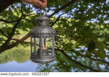 Female Hand Holds A Metal Lantern On A Background Of Green Trees And A Lake. Lantern In His Left Han