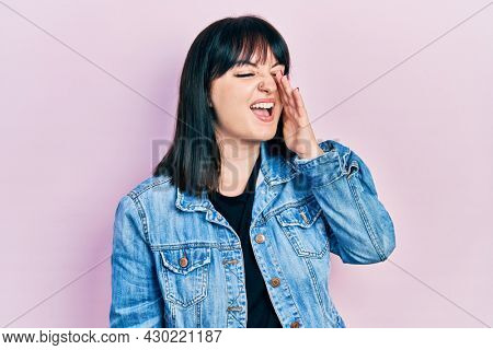 Young hispanic woman wearing casual clothes shouting and screaming loud to side with hand on mouth. communication concept.