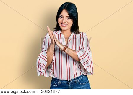 Young hispanic girl wearing casual clothes clapping and applauding happy and joyful, smiling proud hands together