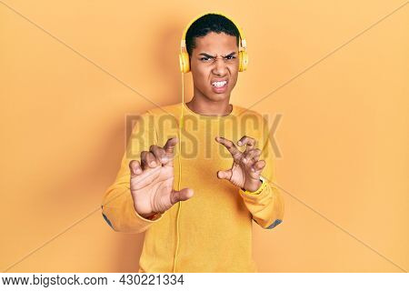 Young african american guy listening to music using headphones disgusted expression, displeased and fearful doing disgust face because aversion reaction.