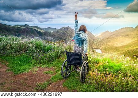 Never Give Up. Rear View Of Young Handicapped Woman Sitting On Wheelchair On Top Of Mountain With Ha