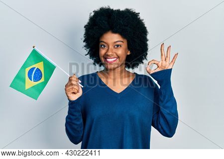 Young african american woman holding brazil flag doing ok sign with fingers, smiling friendly gesturing excellent symbol