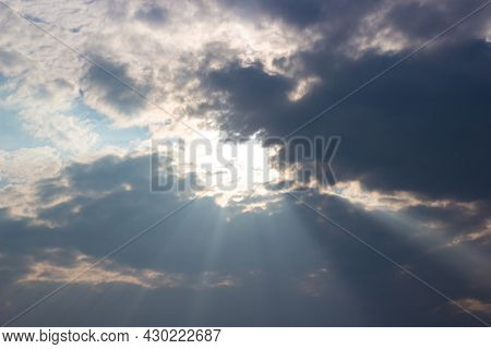 Holy Light Comes From Heaven. Sun Rays Pass Through Dark Cloudy Sky With Bright Pillars Of Light.