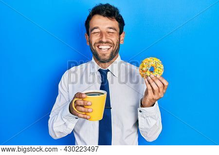 Handsome business man with beard eating doughnut and drinking coffee smiling and laughing hard out loud because funny crazy joke.