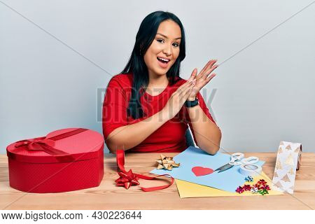 Beautiful hispanic woman with nose piercing doing handcraft creative decoration clapping and applauding happy and joyful, smiling proud hands together