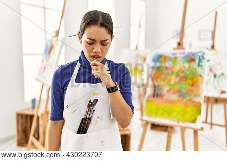Young brunette woman at art studio feeling unwell and coughing as symptom for cold or bronchitis. health care concept.