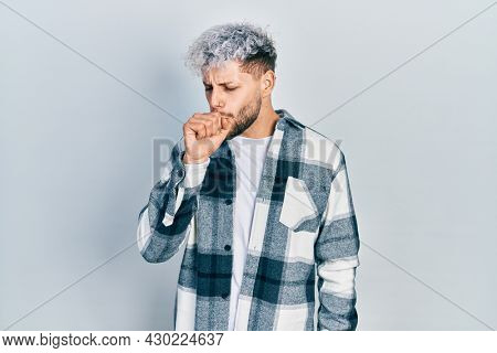 Young hispanic man with modern dyed hair wearing casual shirt feeling unwell and coughing as symptom for cold or bronchitis. health care concept.