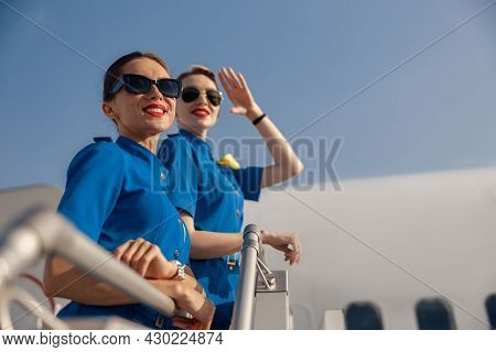 Portrait Of Two Cheerful Air Stewardesses In Blue Uniform And Sunglasses Smiling Away, Standing Toge