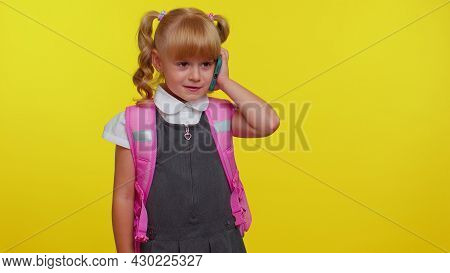 Dissatisfied Nervous Schoolgirl With Backpack Making A Call With Mobile Phone To Mother, Discussing