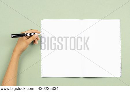 Kid Hand Holding Pen In Left Hand To Write On Blank Open Notebook Over Pastel Green Background. Left