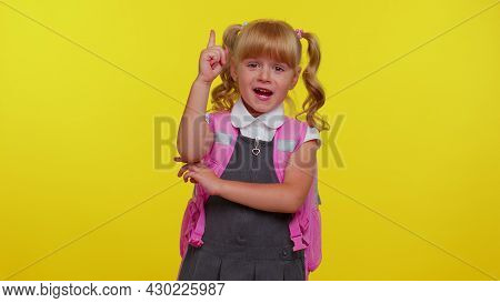 Inspired Cheerful Blond Teenage Schoolgirl Kid In Uniform Pointing Finger Up With Open Mouth, Showin