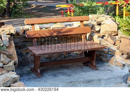 View Of Wooden Bench Surrounded By Natural Stone Masonry