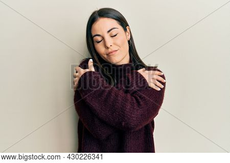 Young brunette woman wearing casual winter sweater hugging oneself happy and positive, smiling confident. self love and self care