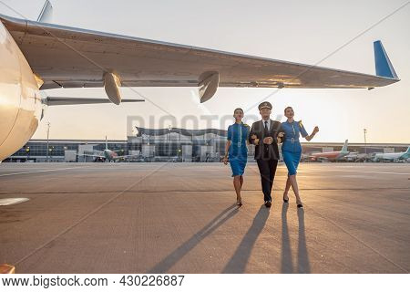 Full Length Shot Of Excited Male Pilot Walking Together With Two Female Flight Attendants In Blue Un