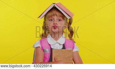 Joyful Little Funny Teenage Schoolgirl Kid Dressed In Uniform Posing With Book On Head Looking Happy