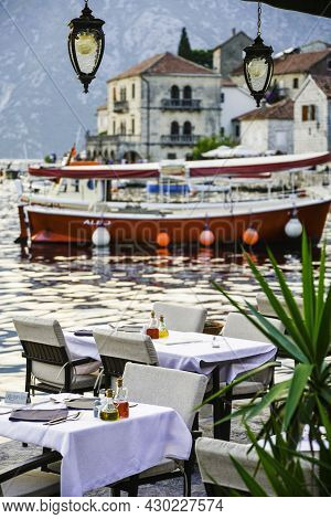 Restaurant Tables Laid Out Awaiting Customers At Sunset By The Waterside,perast,montenegro.