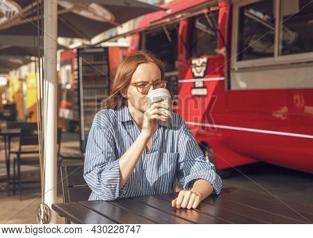 Young Woman In Eyewear Sitting Alone With Collapsible Eco Coffee Cup Near Red Street Food Truck. Mod