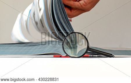 Technical Book With Turning Pages, Male Hand And Magnifying Lens. Engineer Research And Study Concep