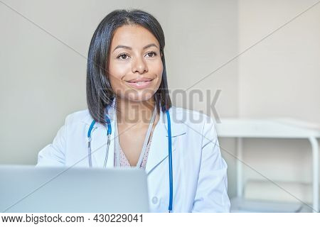 Doc At Work. Smiling Professional Afro American Female Doctor In White Medical Uniform With Stethosc