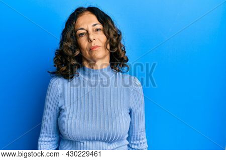 Middle age hispanic woman wearing casual clothes relaxed with serious expression on face. simple and natural looking at the camera.