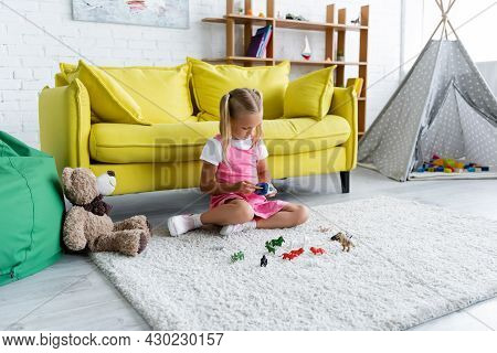 Preschooler Girl Sitting On Carpet And Playing With Toy In Modern Playroom