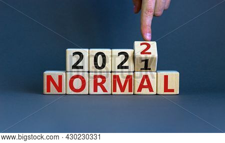 Symbol Of Covid-19 Normal In 2022. Doctor Turns A Wooden Cube And Changes Words 'normal 2021' To 'no