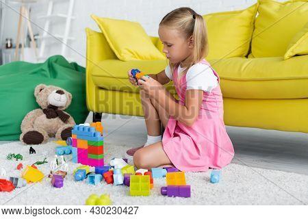 Blonde Girl In Pink Dress Playing Building Blocks On Carpet In Kindergarten Playroom