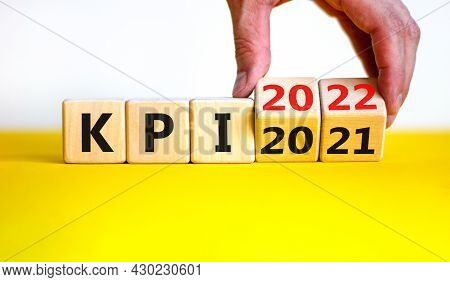 Kpi, Key Performance Indicator Symbol. Businessman Turns Wooden Cubes With Words 'kpi 2021' And 'kpi