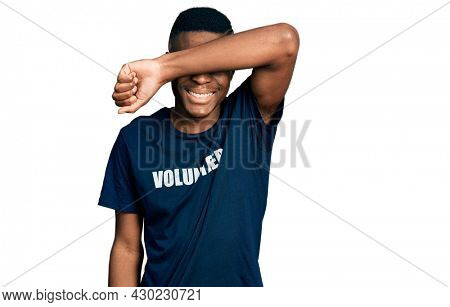 Young african american man wearing volunteer t shirt smiling cheerful playing peek a boo with hands showing face. surprised and exited