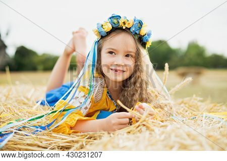 Girl Carries Fluttering Blue And Yellow Flag Of Ukraine In Field.