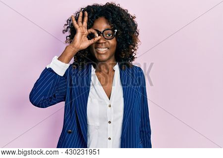 Young african american woman wearing business clothes and glasses doing ok gesture with hand smiling, eye looking through fingers with happy face.