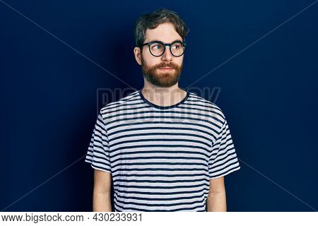 Caucasian man with beard wearing striped t shirt and glasses smiling looking to the side and staring away thinking.