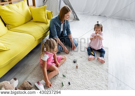High Angle View Of Kindergarten Teacher Looking At Toddler Kid With Down Syndrome Playing With Toy N