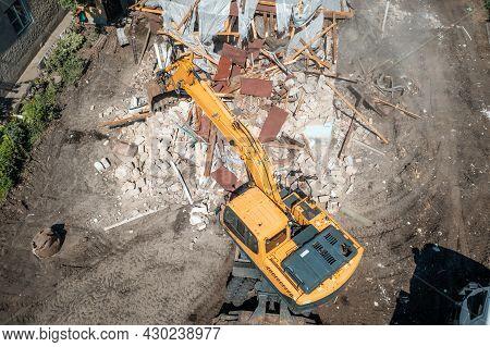 Process Of Demolition Of Old Building Dismantling Aerial View. Excavator Breaking House. Destruction