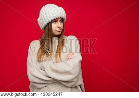 Photo Shot Of Beautiful Offended Resentful Young Dark Blonde Woman Standing Isolated Over Red Backgr