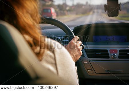 Woman driving a car, close up of her hand at the steering wheel. View from behind
