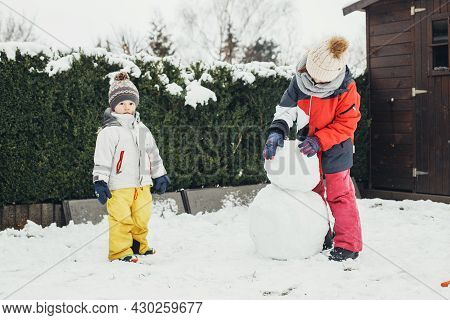Snow Time, Games In The Snow. Winter Holidays. Cute Caucasian Children Brother And Sister Make A Sno