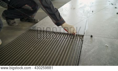 Installing A Large Ceramic Tile. Workers Lay Large Tiles On The Floor.