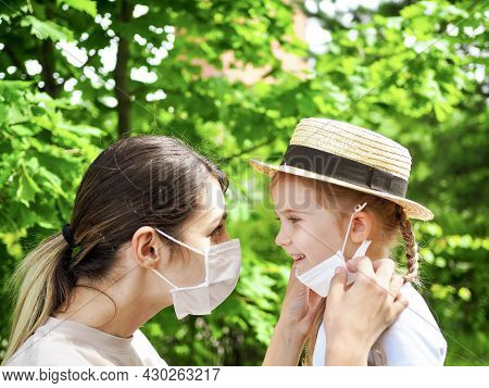 Little Girl And Mother Wearing Protect Medical Masks Walking In Park On Sunny Day. Mother Putting Ma