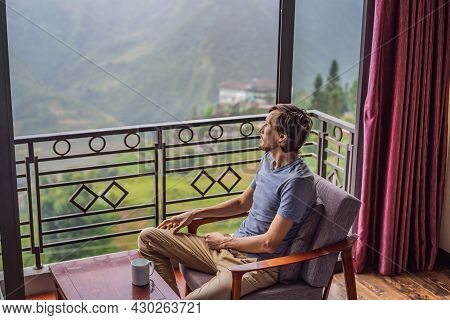 A Young Man Holding Coffee Cup While Sittinhg On Chair On Balcony , Looking At Mountains And Green N