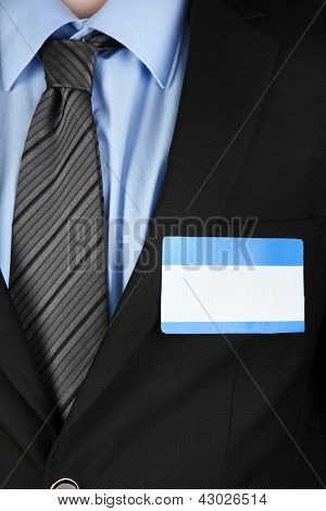 Blank nametag on businessman's black suit close up