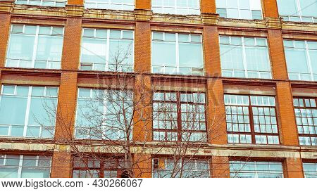 The Wall Of An Old Industrial Building With Large Windows. Industrial Architecture Of The Early 20th