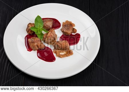 Delicacy Fried pork meat with zucchini puree and berries sauce decorated with mint on white plate on black wooden background