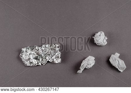 Minimalist Composition With Crumpled Foil And White Paper Against A Gray Background. Pieces Of Alumi