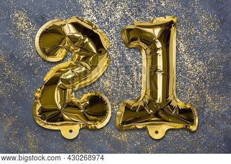 The Number Of The Balloon Made Of Golden Foil, The Number Twenty-one On A Gray Background With Sequi