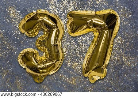 The Number Of The Balloon Made Of Golden Foil, The Number Thirty-seven On A Gray Background With Seq
