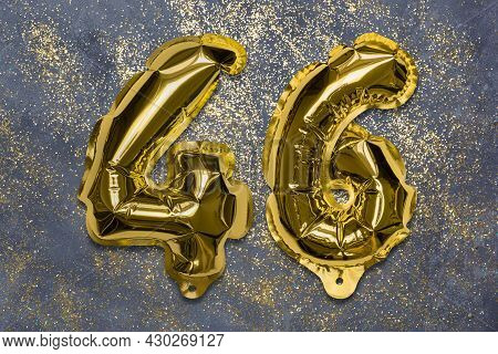 The Number Of The Balloon Made Of Golden Foil, The Number Forty-six On A Gray Background With Sequin